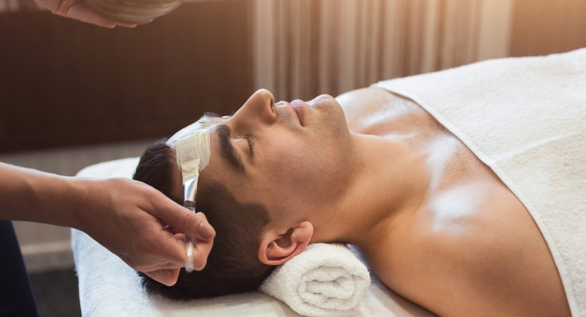 Man getting facial nourishing mask by beautician at spa salon, closeup. Apply face mask, spa beauty treatment and skincare.