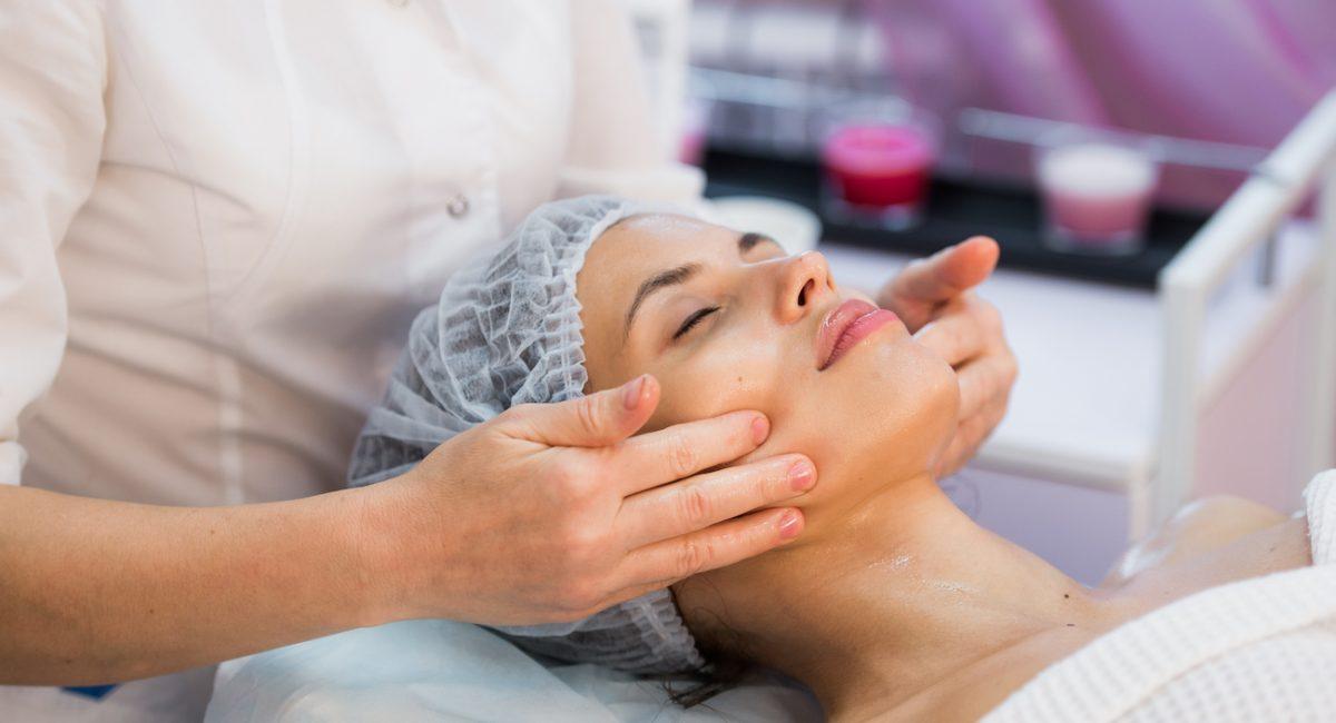 Young woman enjoying facial at spa salon.